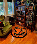 Large rug with scary pumpkin face in black with yellow edges. Photographed in a livingroom with hardwood floors.