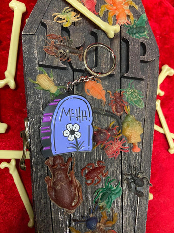 "Close up of enamel keychain with ""mehh"" across it one casket RIP across it and plastic bones around it."