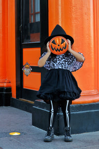Little girl in a witches hat and costume holding a glitter orange jack o lantern pumpkin purse in front of her face with a Love Pain and Stitches logo next to her.