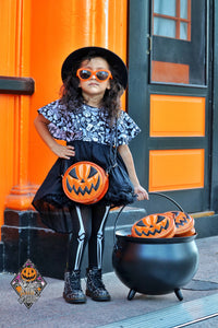 Little girl in a witches hat and costume holding a glitter orange scary smiling faces  jack o lantern pumpkin purse crossbody bag and holding a cauldron full of orange sparkly jack o lantern purses. with a Love Pain and Stitches logo next to her.