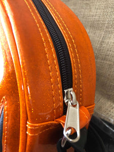 Orange sparkly bag with orange stitches and a black zipper with a chrome zipper pull.