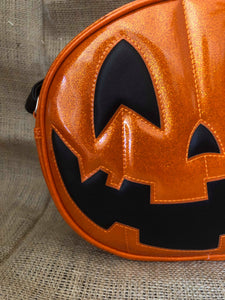 Half of an Orange jack o lantern pumpkin bag with orange stitching and a black smiling face