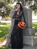 Woman in a graveyard wearing an orange jack o lantern pumpkin bag with orange stitching and a black scary smiling face