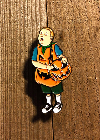 Boy with Pumpkin Costume with a pumpkin purse lapel pin on a wooden background
