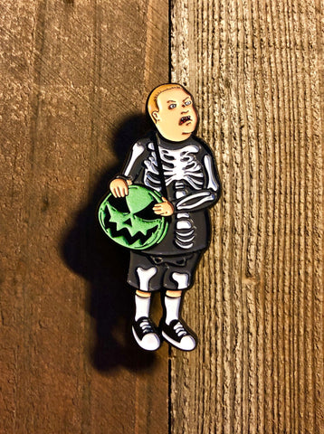 Boy with Skeleton Costume with a pumpkin Bag lapel pin on a wooden background