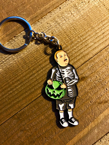 Boy in a skeleton costume with a pumpkin bag keychain on a wooden background