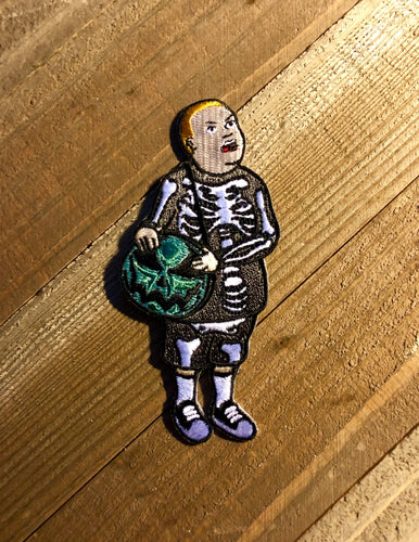 Boy with Skeleton Costume and Pumpkin purse patch on a wooden background