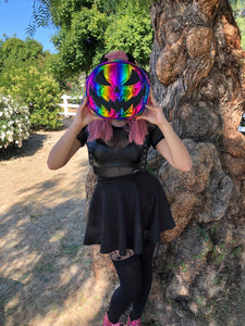 Woman standing next to tree holding a rainbow jack o lantern pumpkin crossbody bag in front of her face.