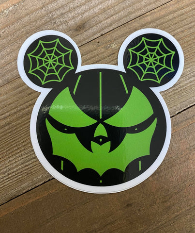 Sticker of all black pumpkin with green face with bat mouth. Two spider webs in black and green on either side of the top of the pumpkin.