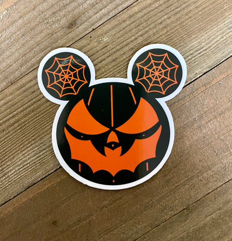 Sticker of all black pumpkin with orange face with bat mouth. Two spider webs in black and orange on either side of the top of the pumpkin.