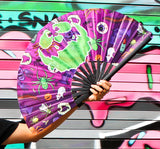 Girl hold purple fan with pumpkin face in front of graffiti wall.