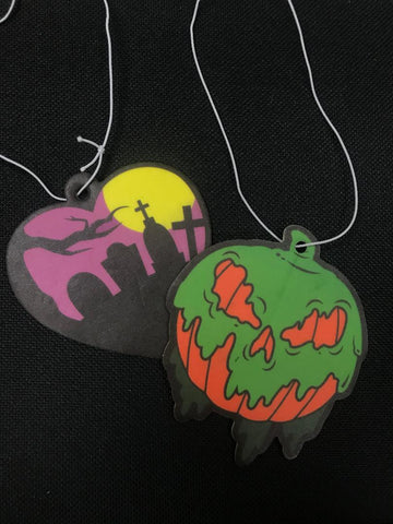 Hanging air fresheners. One heart shaped with a graveyard scene, the other a pumpkin covered in goo with an evil face.