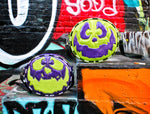 Monster bags photographed against graffiti wall. One in purple and green and the other in green and purple.
