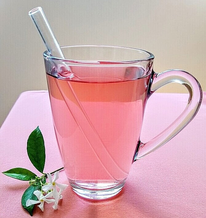ToMA glas straw in glacier clear in a clear glass mug of cherry hibiscus tea on pink linen tablecloth with jasmine bloom.