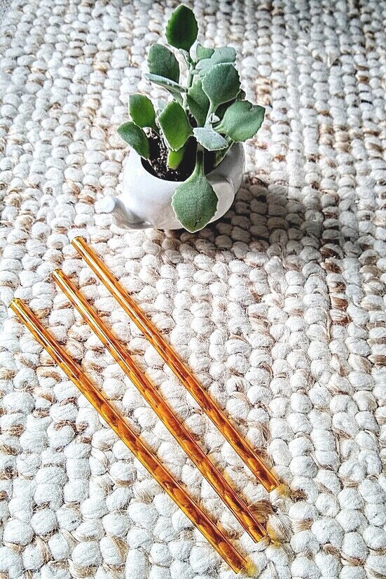 Photo of three ToMA glass straws in artisanal amber on textured carpet with small white porcelain elephant planter with succulent.