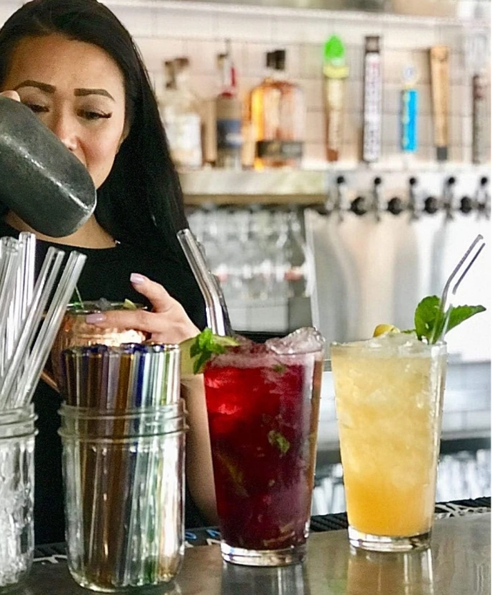 Young Asian woman bartender preparing cocktails at a bar. Two drinks with glass straws. Barware.