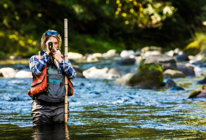 Woman biologist standing in river doing research for The Freshwater Trust, a nonprofit conservation organzation in Portland, Oregon.