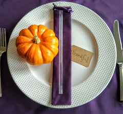 """Photo of ToMA glass straw in glacier clear as party favor on velveteen gift bag in grape on white plate with small pumpkin and handwritten """"Thankful"""" tag."""
