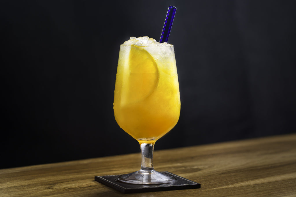 Photo of orange cocktail with ice and orange slice featuring a ToMA Glass Straw in pacific blue. Beautiful, durable, affordable glass straw packages for bars, restaurants, cafes, weddings.