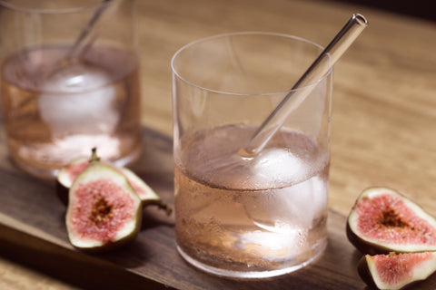 Photo of two glasses with halved figs, pink drink and beautiful glass straw in rose garden pink from ToMA Glass Straws. Photo: Magela Crosignani