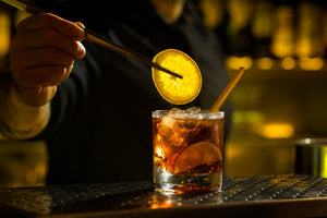 Photo of bartender's hand with tongs holding a lemon slice as he prepares to garnish a brown cocktail with a ToMA Glass Straw in artisanal amber. Affordable glass straw packages for bars and restaurants, craft cocktails. Photo: Magela Crosignani