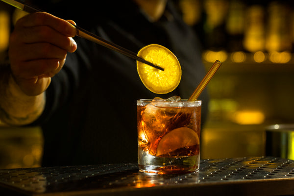 Photo of bartender placing a lemon slice in a cocktail featuring a 6-inch reusable glass straw in artisanal amber by ToMA Glass Straw, the go-to glass straw source for bars, restaurants, hotels, resorts, cafes, private dining rooms.