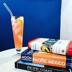 ToMA glass straw in bent glacier clear in tall orange cocktail against blue wall with stack of books about Mexico travel and Pacific Northwest birds.