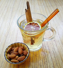 ToMA glass straw in artisanal amber in hot tea with cinnamon bark and dehydrated lemon. Small ceramic bowl of almonds.