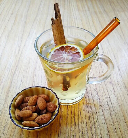 ToMa glass straw in artisanal amber in hot herbal tea with dehydrated citrus and cinnamon stick, ceramic bowl of almonds, wood table.
