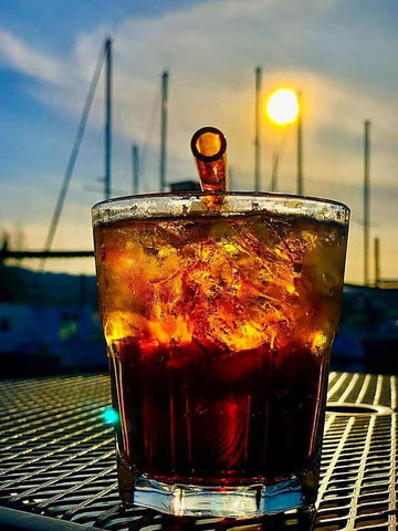 Photo of amber cocktail on table at sunset near sailboats with 6-inch reusable glass straw in artisanal amber by ToMA Glass Straws. Affordable glass straws for businesses, events, home use.