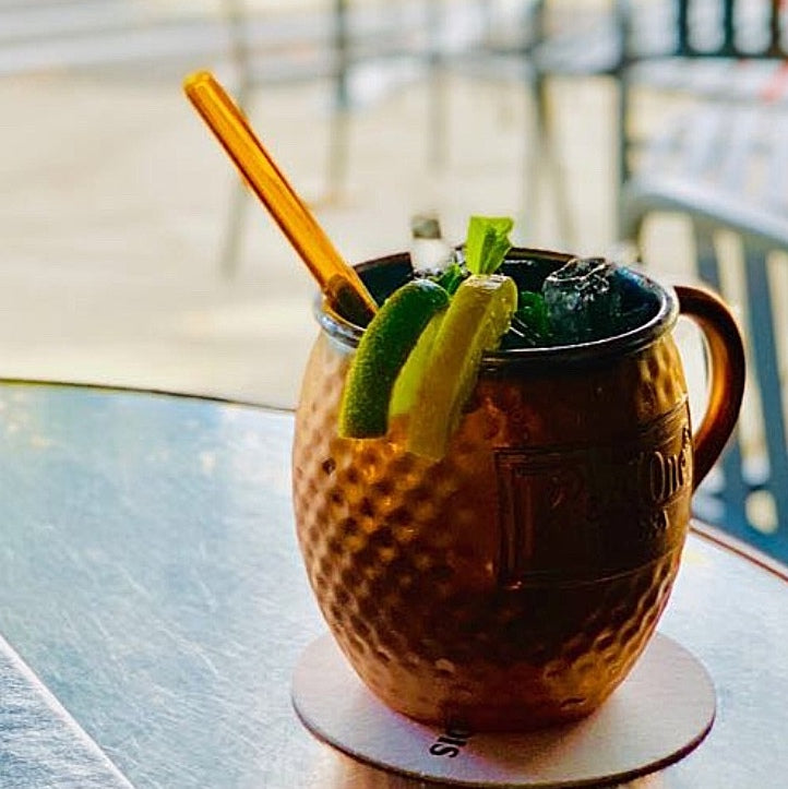 Photo of a Moscow Mule cocktails in a copper mug filled with ice and garnished with lime and lemon wedges. Featuring a reusable 6