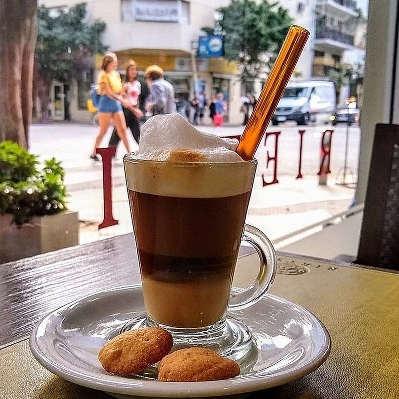 Photo of layered coffee beverage with foam in clear mug on a white saucer with two cookies. Featuring a reusable 6-inch ToMA glass straw in artisanal amber. Street scene with pedestrians in sunny city scene.
