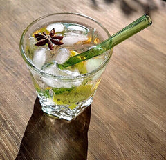 ToMA glass straw in forest green in ice-filled cut glass with star anise garnish on scuffed wood table.