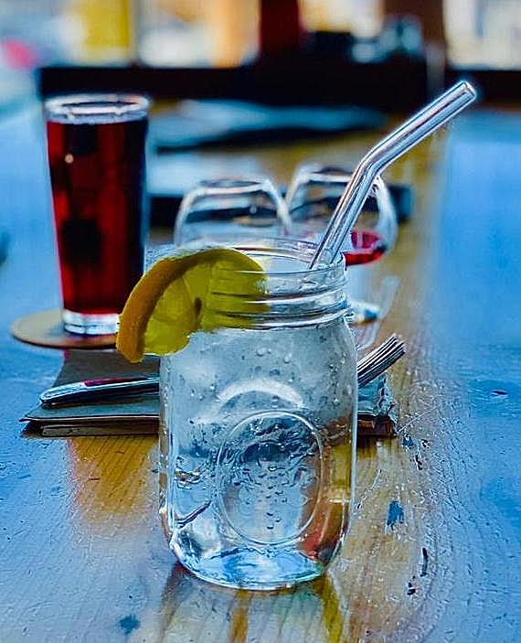 Photo of jar of water in a restaurant bar with a tall 9=inch clear glass straws from ToMA Glass Straws in Portland, Oregon. Part of the Seascape collection of blue and clear straws for bars, restaurants, weddings, events.