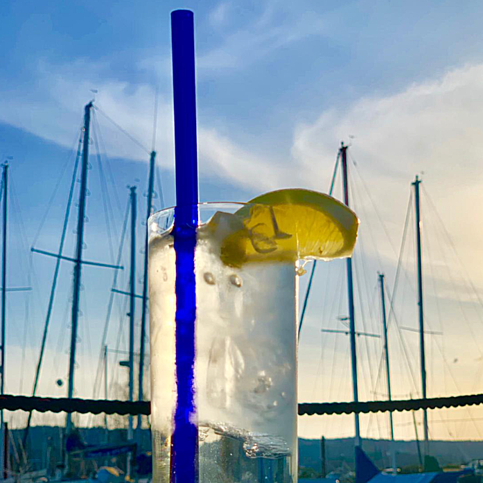 Photo of tall clear cocktail with lemon wedge, featuring a reusable 9-inch ToMA glass straw in pacific blue against blue sky and sailboats at sunset.