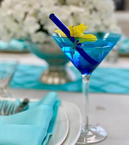 Photo of blue beverage in glass with 6-inch glass straw in pacific blue by ToMA Glass Straws, the go-to glass straw wholesale source for businesses and events.