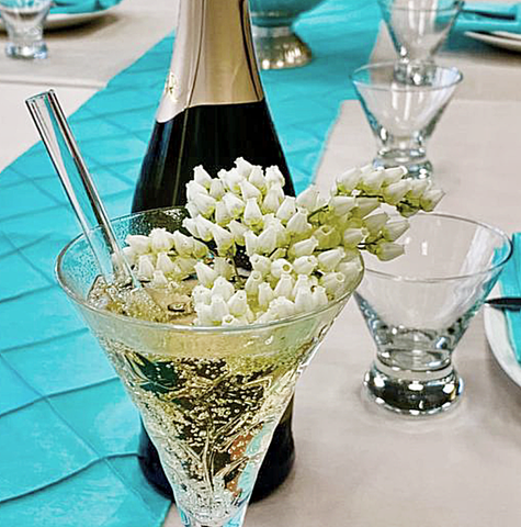 Photo of ToMA glass straw in glacier clear in champagne glass garnished with white spring flowers on white linen.