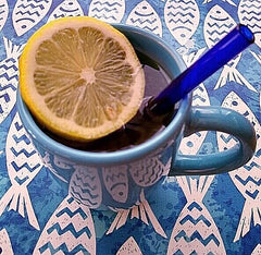 ToMA glass straw in pacific blue in blue ceramic mug with lemon slice on fish print tablecloth.