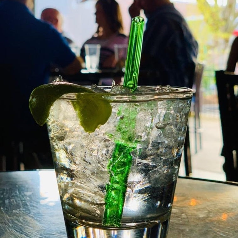 Photo of clear cocktail with a lime peel garnish, featuring a reusable 6-inch ToMA glass straw in forest park green. Restaurant bar setting, customers in outdoor dining area enjoying drinks, mocktails, beverages.