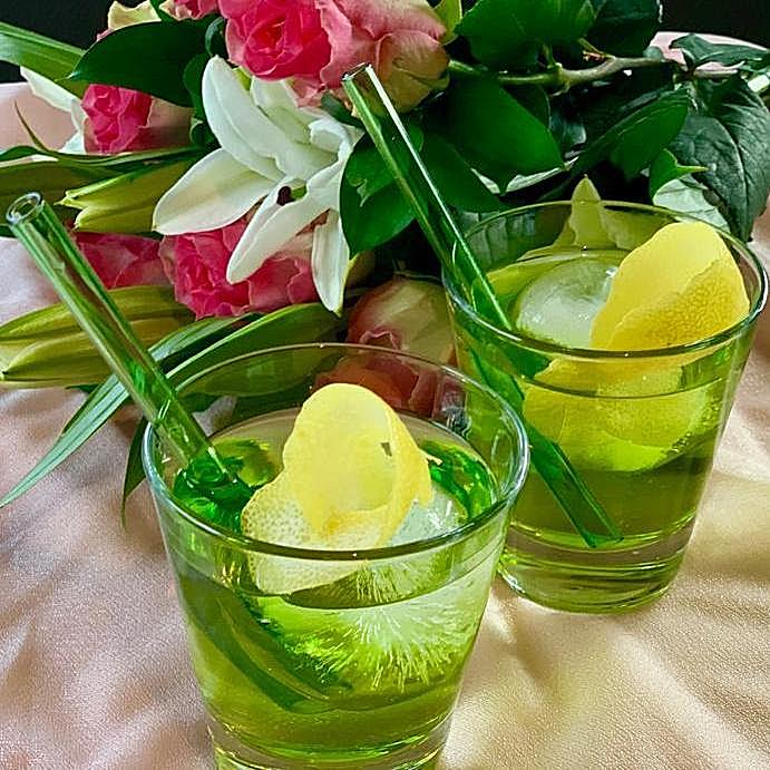 Photo of two cocktails in green glasses with round ice cube and lemon peel garnish, featuring two reusable 6-inch ToMA glass straws in forest park green. Linen table cloth, white lilies, pink roses, wedding, hotel, event venue.
