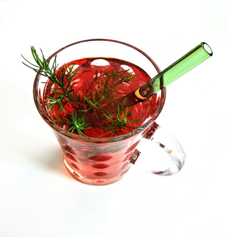 ToMA glass straw in forest green in clear glass mug of hot puer tea with greenery garnish and white background.