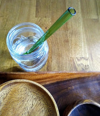 ToMA glass straw in forest green in clear glass of water with wooden bowls and tray.