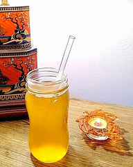 Photo of ToMA glass straw in hot gold tea on wood table with orange leaf candle.