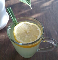 ToMA glass straw in forest green in hot lemon water in glass mug with lemon slice. Wood table, plant. Protect tooth enamel.