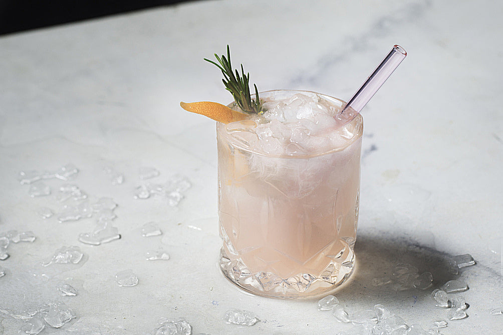 Photo of pale pink cocktail with rosemary sprig and orange peel garnish featuring a ToMA glass straw in rose garden pink. Beautiful, elegant, affordable glass straws for bars, restaurants, cafes, events, weddings, home use. Photo: Magela Crosignani