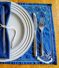 ToMA glass straw in glacier clear with navy blue cloth napkin tied with white string on white plate placed in Japanese sashiko embroidered cloth.