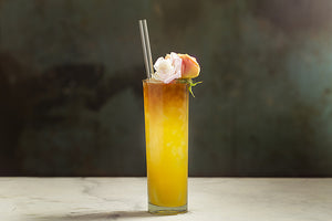 Photo of tall golden cocktail garnished with two small rosebuds and featuring a ToMA Glass Straw in glacier clear. Beautiful, elegant, and affordable glass straws for bars, restaurants, cafes, events, weddings. Photo: Magela Crosignani