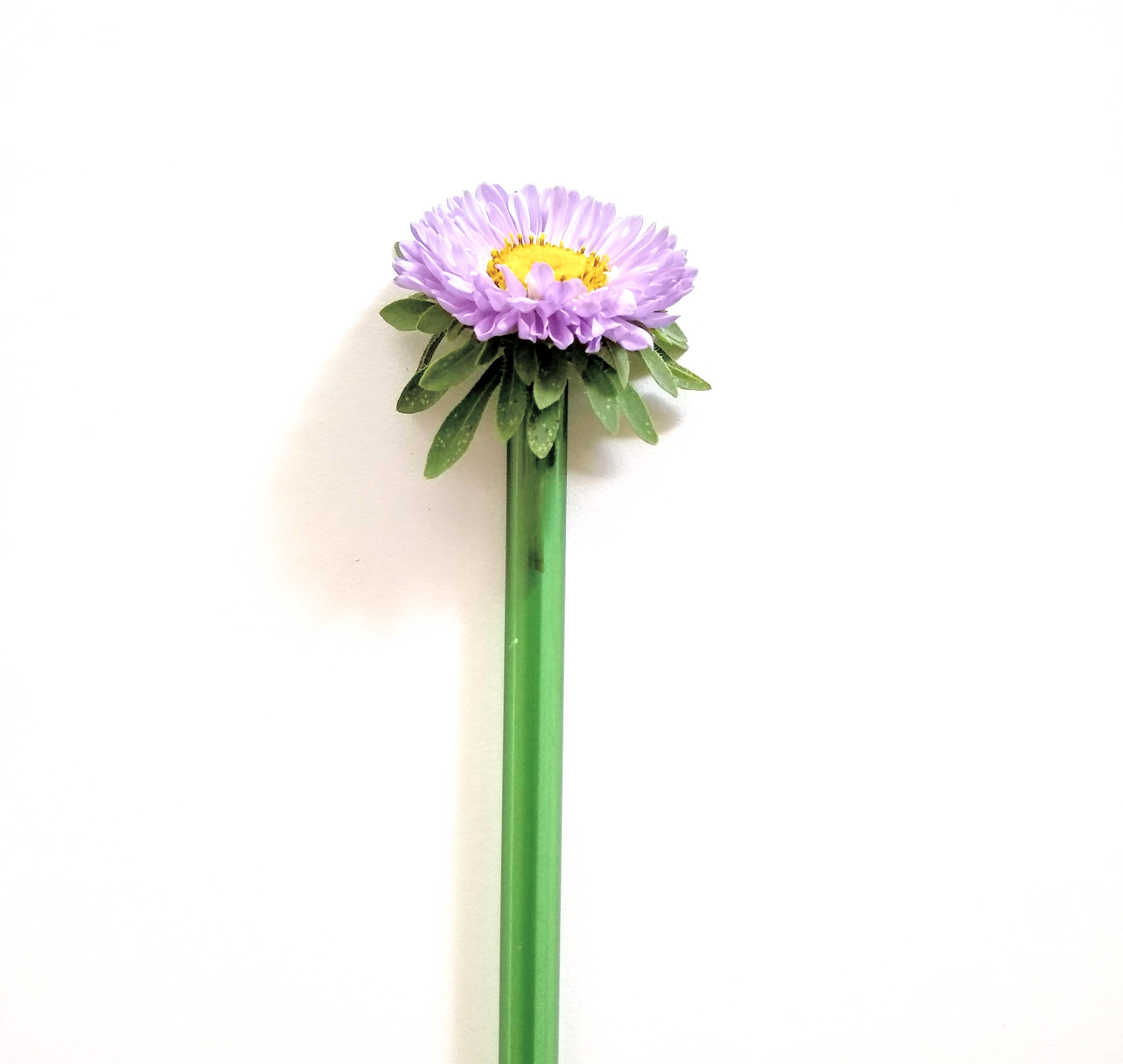 green ToMA glass straw with fresh flower slipped inside as gift at a garden party