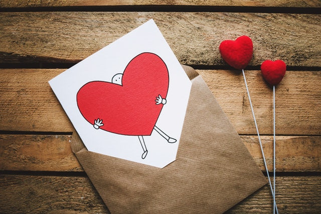 Photo of card with drawing of person holding a heart and brown envelope. Photo by  pexels.com/@freestocks