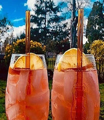 Photo of ToMA glass straw in artisanal amber in two glasses of orange cider outdoors.